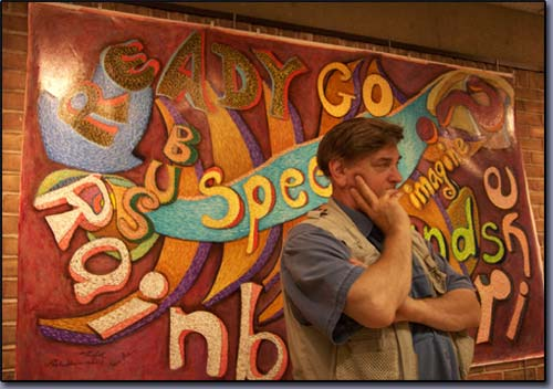 James Homer Brown, metro Detroit Michigan artist contemplates next brushstrokes for the Words at Play mural currently on exhibit at the Troy michigan public library